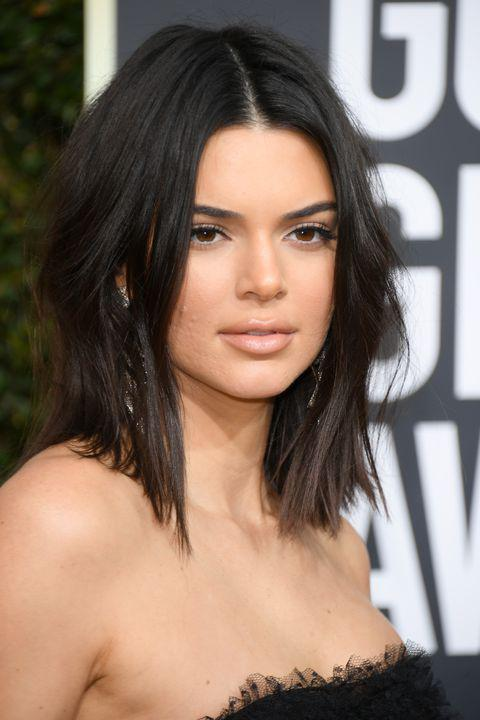Kendall Jenner stands out in the crowd with a rich black color and center part contrast.