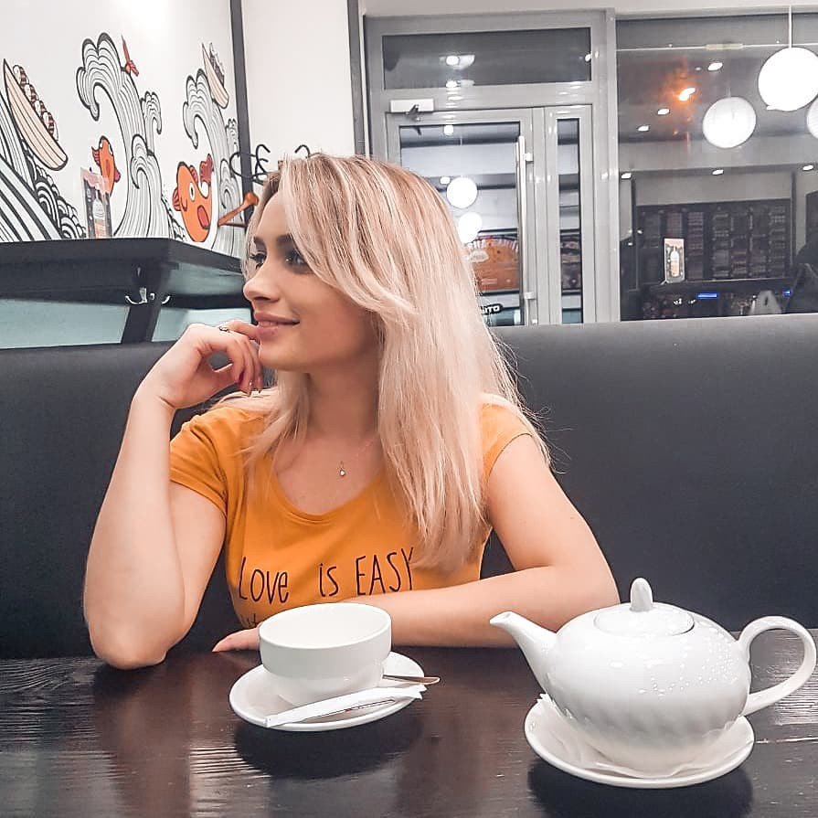 Aleksandra Glance blond hairstyle, hair coloring, coffee cup